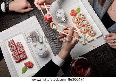 Japanese food, a man and a woman eating maki sushi roll with chopsticks at a table elegantly served - stock photo