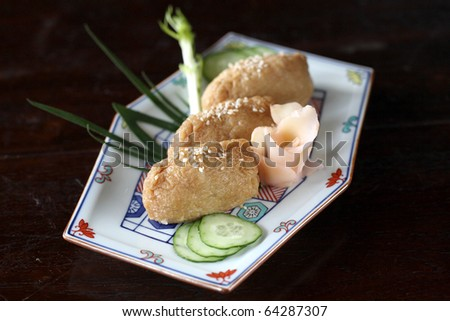 japanese food Inari sushi bean curd with dark brown wood pattern - stock photo