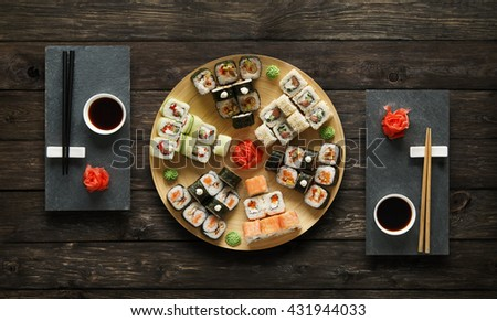 Japanese food restaurant, avocado sushi maki roll plate or platter set. Set for two with chopsticks, ginger, soy, wasabi. Sushi at black stone mat and rustic wood background. Top view, flat lay. - stock photo