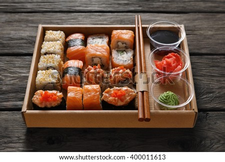 Japanese food restaurant, catering, sushi maki gunkan roll plate or platter set. Chopsticks, ginger, soy sauce, wasabi. Sushi at rustic wood background in take away, sushi set delivery box.  - stock photo