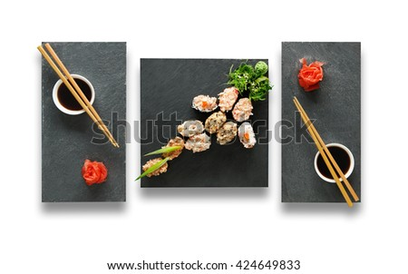 Japanese food restaurant, sushi gunkan plate or platter set. Set for two with chopsticks, ginger, soy sauce and wasabi. Sushi at black stone isolated at white background. Top view, Flat lay. - stock photo
