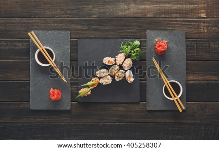 Japanese food restaurant, sushi gunkan roll plate, platter set. Creative food. Set for two with chopsticks, ginger, soy, wasabi. Sushi at rustic wood background and black stone. Flat lay, top view.  - stock photo