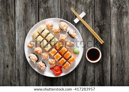 Japanese food restaurant, sushi maki gunkan roll plate or platter set. Chopsticks, ginger and wasabi. Sushi at white round plate, rustic wood background. Top view with soy sauce - stock photo