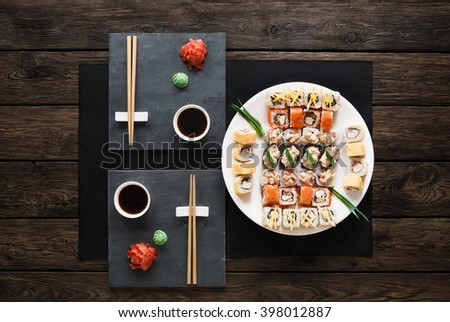 Japanese food restaurant, sushi maki gunkan roll plate or platter set. Set for two with chopsticks, ginger and wasabi. Sushi at rustic wood background and black stone. Top view at black. Flat lay.  - stock photo