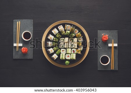 Japanese food restaurant, sushi maki gunkan roll plate or platter set. Set for two with chopsticks, ginger, soy, wasabi. Sushi at rustic wood background and black stone. Top view at black - stock photo