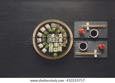 Japanese food restaurant, sushi maki gunkan roll plate or platter set. Set for two with chopsticks, ginger, soy, wasabi. Sushi at rustic wood background and black stone. Top view at black, copyspace - stock photo