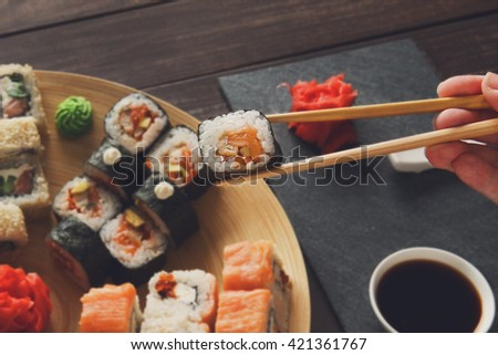 Japanese food restaurant, sushi maki roll plate, platter set. Hand take roll. Set for two with chopsticks, ginger, soy, wasabi. Sushi at rustic wood background and black stone. POV at black. Closeup. - stock photo