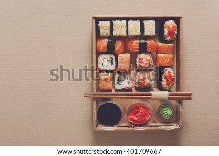 Japanese food restaurant, sushi rolls, gunkan plate or platter set. Copyspace. Chopsticks, ginger, soy sauce and wasabi. Sushi at carton, paperboard background in take away, delivery box. Top view.  - stock photo