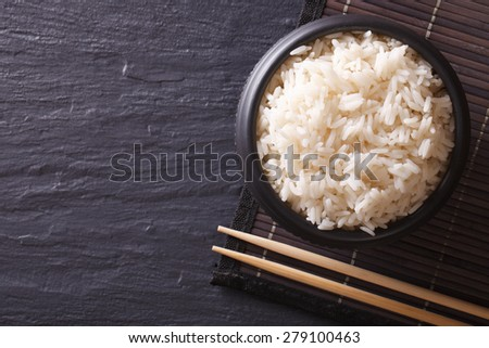 Japanese food: rice in a black bowl and chopsticks. horizontal view from above  - stock photo