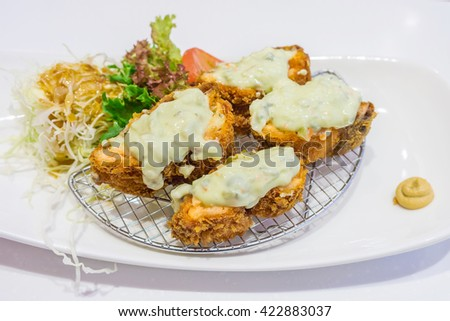 Japanese fried breaded chicken with salad cream served with vegetable salad - stock photo