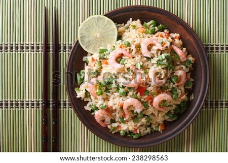 Japanese fried rice with seafood and vegetables on a plate close-up, horizontal view from above  - stock photo