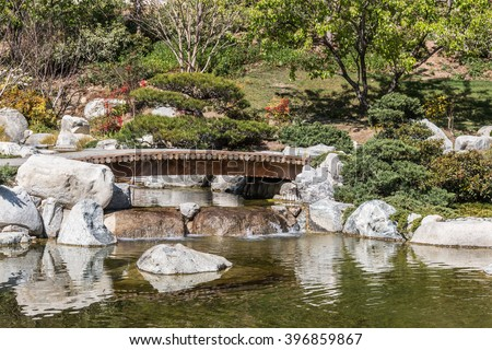Japanese garden bridge over a pond. Trees and shrubbery. Reflections of rocks in water.  - stock photo