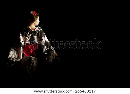 Japanese geisha looking at the light throwing open wings - stock photo