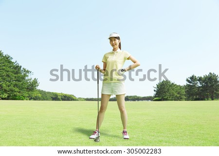 Japanese golfer standing on the golf course - stock photo