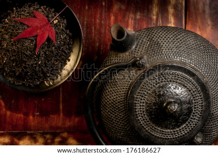 Japanese iron teapot and heap of tea leaves from top. Red mable leaf on top of tea leaves. Mahogany background. Asian culture background. Horizontal photography no people. - stock photo