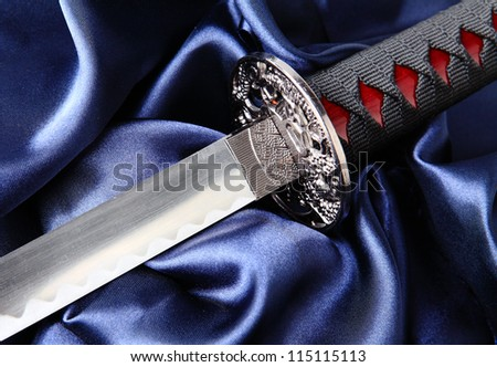 Japanese katana sword on blue satin background - stock photo