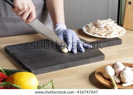 Japanese knife Cutting garlic on a cutting board - stock photo