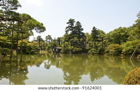 Japanese lake with a waterfall and one of the famous lanterns - stock photo