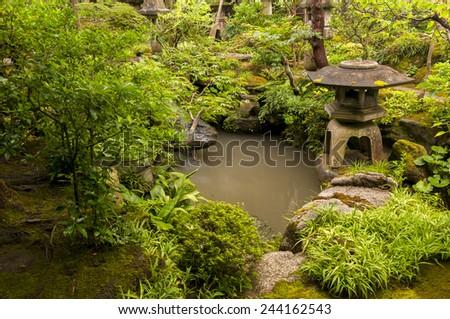 Japanese lantern near the pond - stock photo
