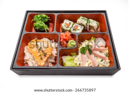 Japanese Meal in a Box (Bento) isolated on white background - baked salmon with rice, salad with chicken, sushi & rolls - stock photo