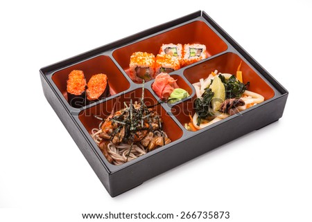 Japanese Meal in a Box (Bento) isolated on white background - Japanese noodles with meat and vegetables, seafood salad, sushi and rolls - stock photo