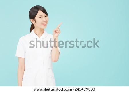 Japanese nurse pointing side - stock photo
