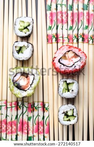 Japanese rolls on a background of chopsticks - stock photo