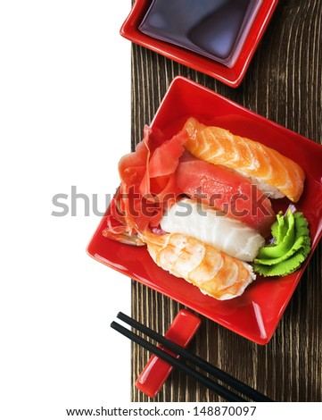Japanese seafood sushi and chopsticks on a red plate - stock photo