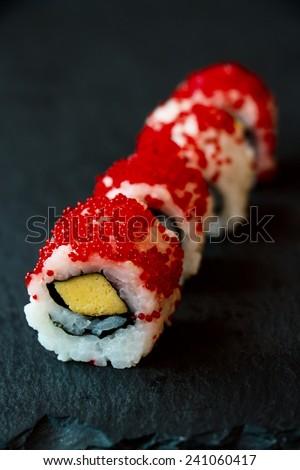 Japanese seafood sushi rolls on black background. Selective focus - stock photo
