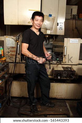 Japanese small business owner full length portrait/Satisfaction guaranteed 2/ A full length portrait of a Japanese small business owner inside his small metal workshop. - stock photo