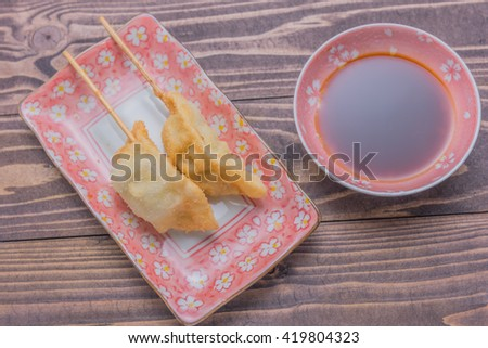 japanese style fried dumpling gyo-za witch Sho-yu sauce on dish, wooden table background - stock photo