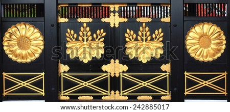 Japanese-Styled Gate ornamented with Golden Flower Symbols on black wooden background - stock photo