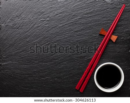Japanese sushi chopsticks and soy sauce bowl on black stone background. Top view with copy space - stock photo
