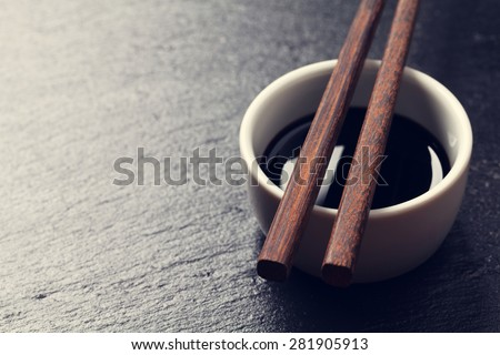 Japanese sushi chopsticks over soy sauce bowl on black stone background. Top view with copy space. Toned - stock photo