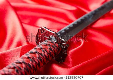 Japanese sword takana on red satin background - stock photo