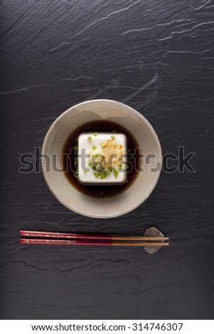 Japanese tofu, Japanese soft cold tofu with sauce in a dish on dining table with chopstick - stock photo
