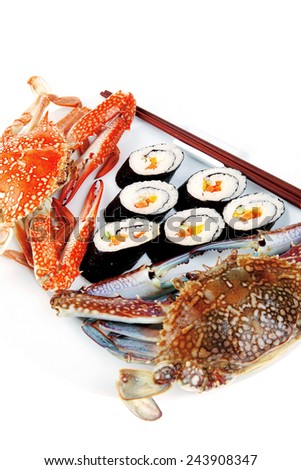 Japanese traditional Cuisine - Roll with Cucumber , Cream Cheese with raw Tuna and Salmon inside. on black dish with red and blue crabs . - stock photo