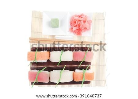 Japanese traditional cuisine - Set of Tuna (maguro) Salmon (sake) and Eel (unagi) Nigiri Sushi  with Wasabi  and Ginger on bamboo mat isolated over white background - stock photo