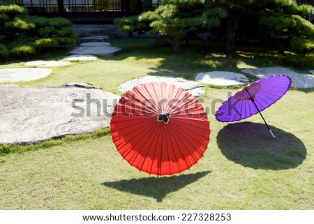 Japanese traditional red umbrella in Japanese garden - stock photo