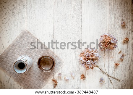 Japanese traditional sake cup and bottle on a wooden background - stock photo
