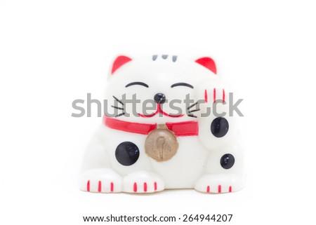 Japanese white beckoning cat also known as a Maneki Neko raising her left paw - stock photo