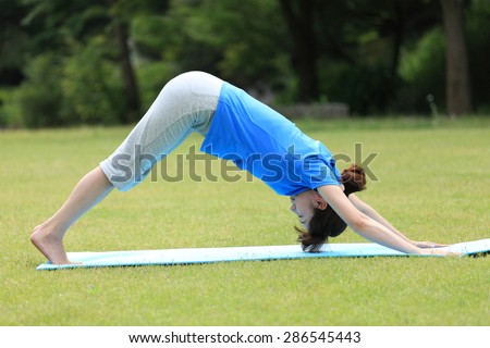 Japanese woman doing yoga Downward-Facing Dog - stock photo
