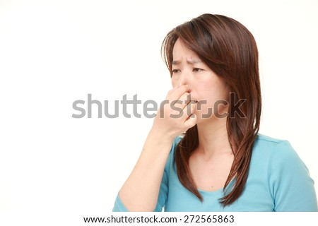 Japanese woman holding her nose because of a bad smell - stock photo