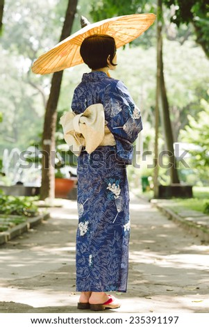 Japanese woman in traditional dress enjoying nature in the park, rear view - stock photo