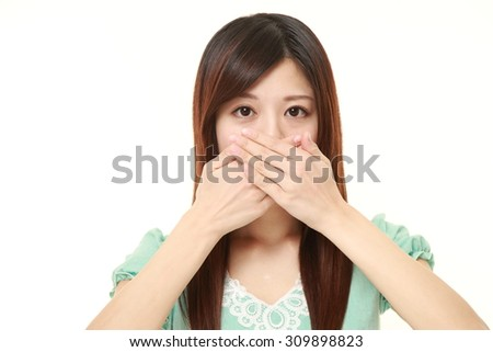 Japanese woman making the speak no evil gesture - stock photo