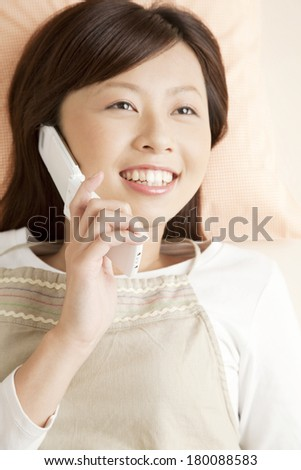 Japanese woman on the phone while lying down - stock photo