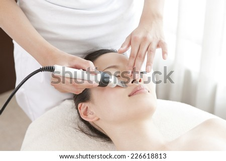 Japanese woman receiving face treatment - stock photo