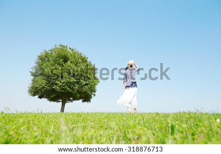 Japanese woman standing on the green field - stock photo