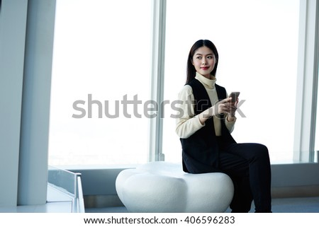 Japanese young female student is using mobile phone, while is waiting the beginning of lectures in modern hing business school. Asian woman sitting in modern interior near copy space for your content - stock photo