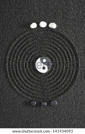 japanese zen garden with yin and yang stone - stock photo